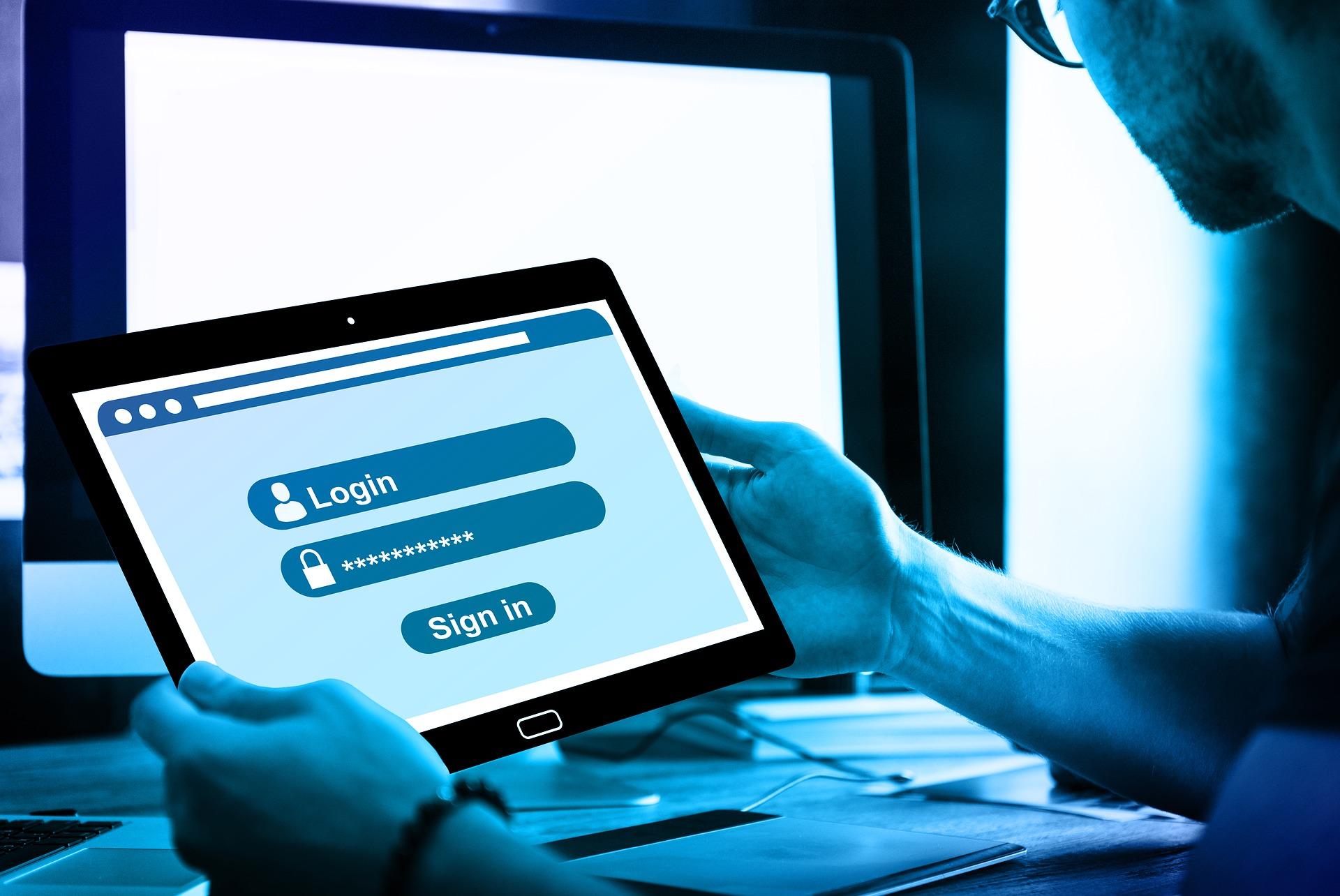 男性が持っているタブレットに、webサイトのログイン画面が表示されている。