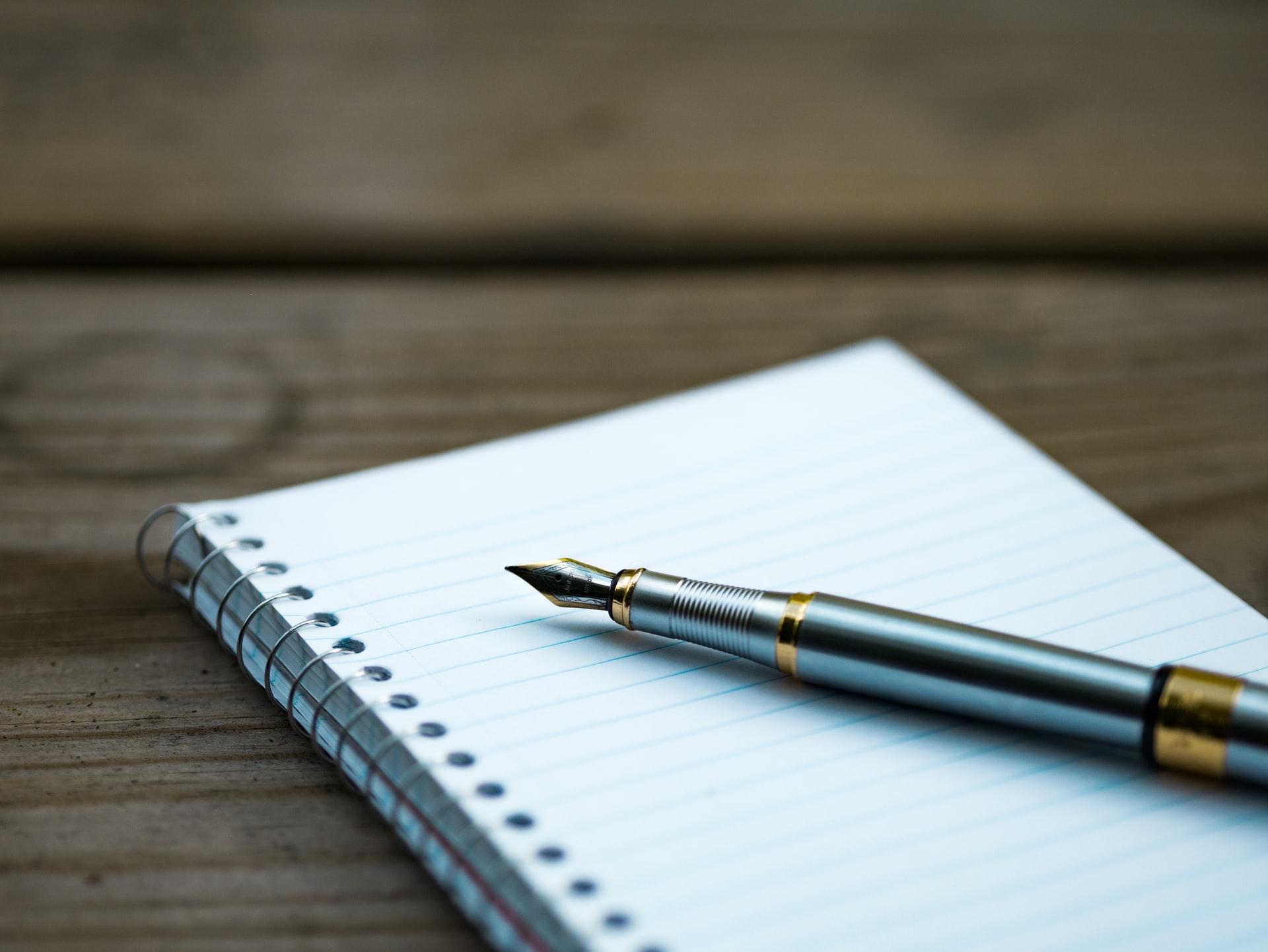 ノートとペンが机に置かれている。