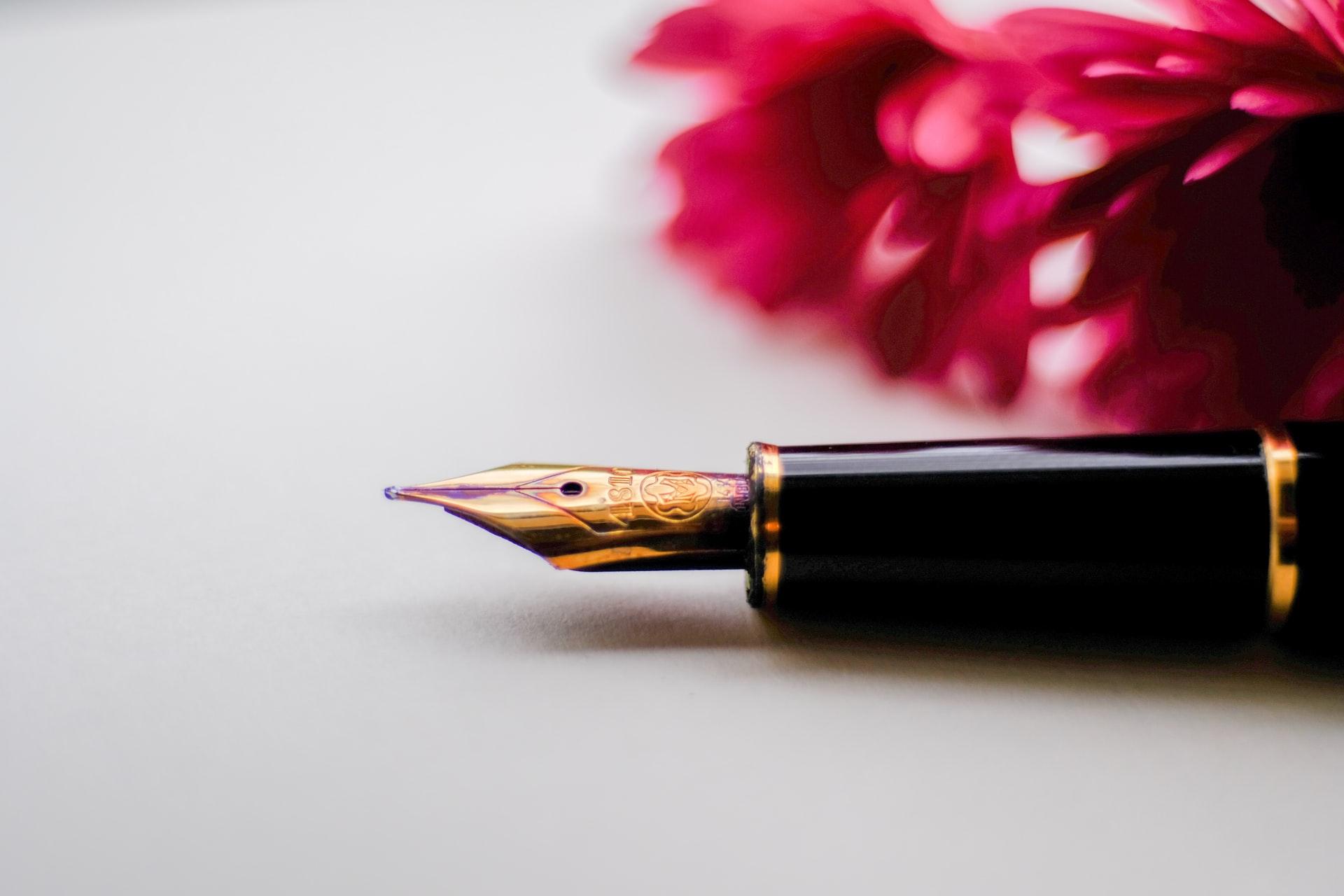 万年筆が白い紙の上に置かれている。
