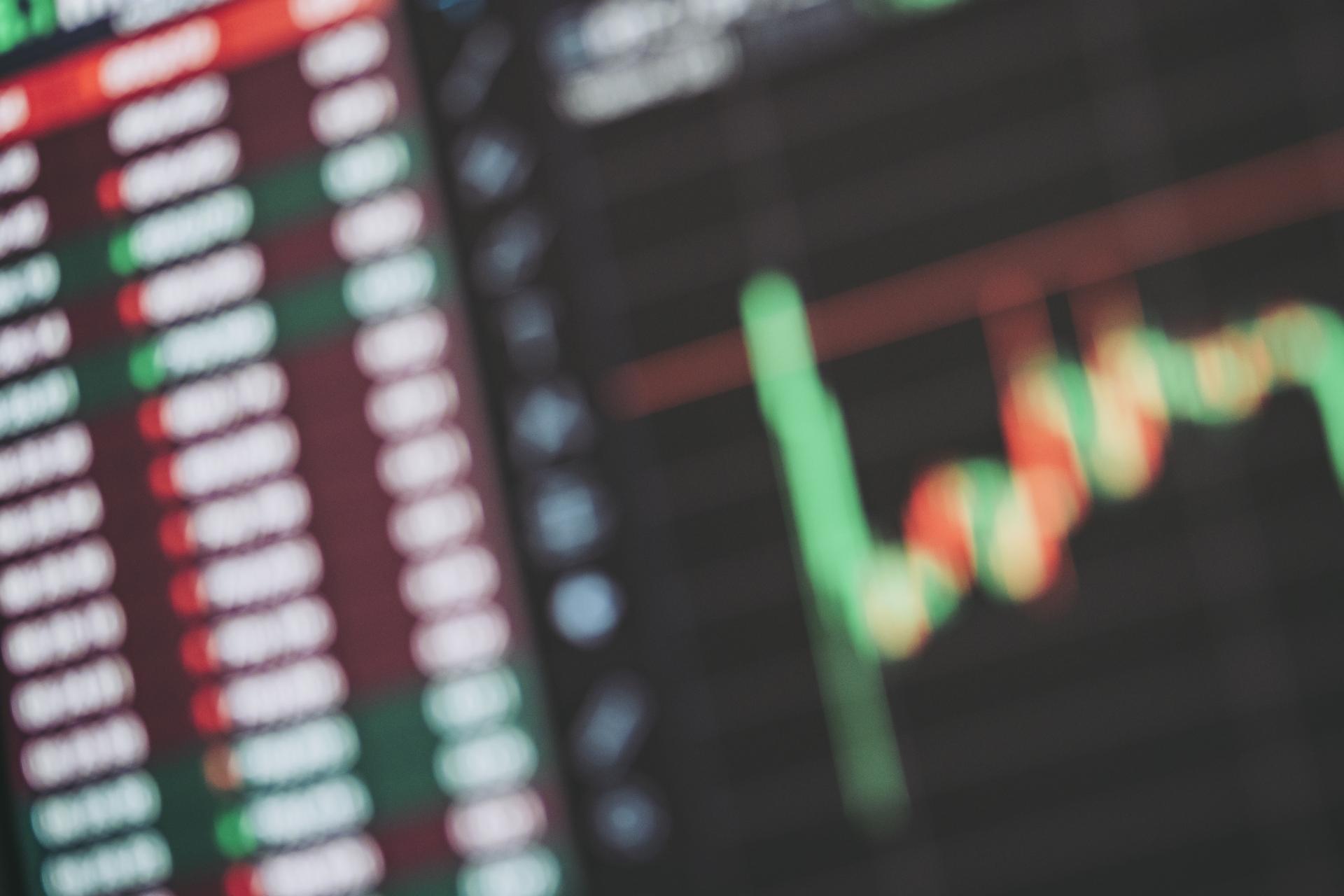 株価ボードがぼかして写っている。株式取引のイメージ。