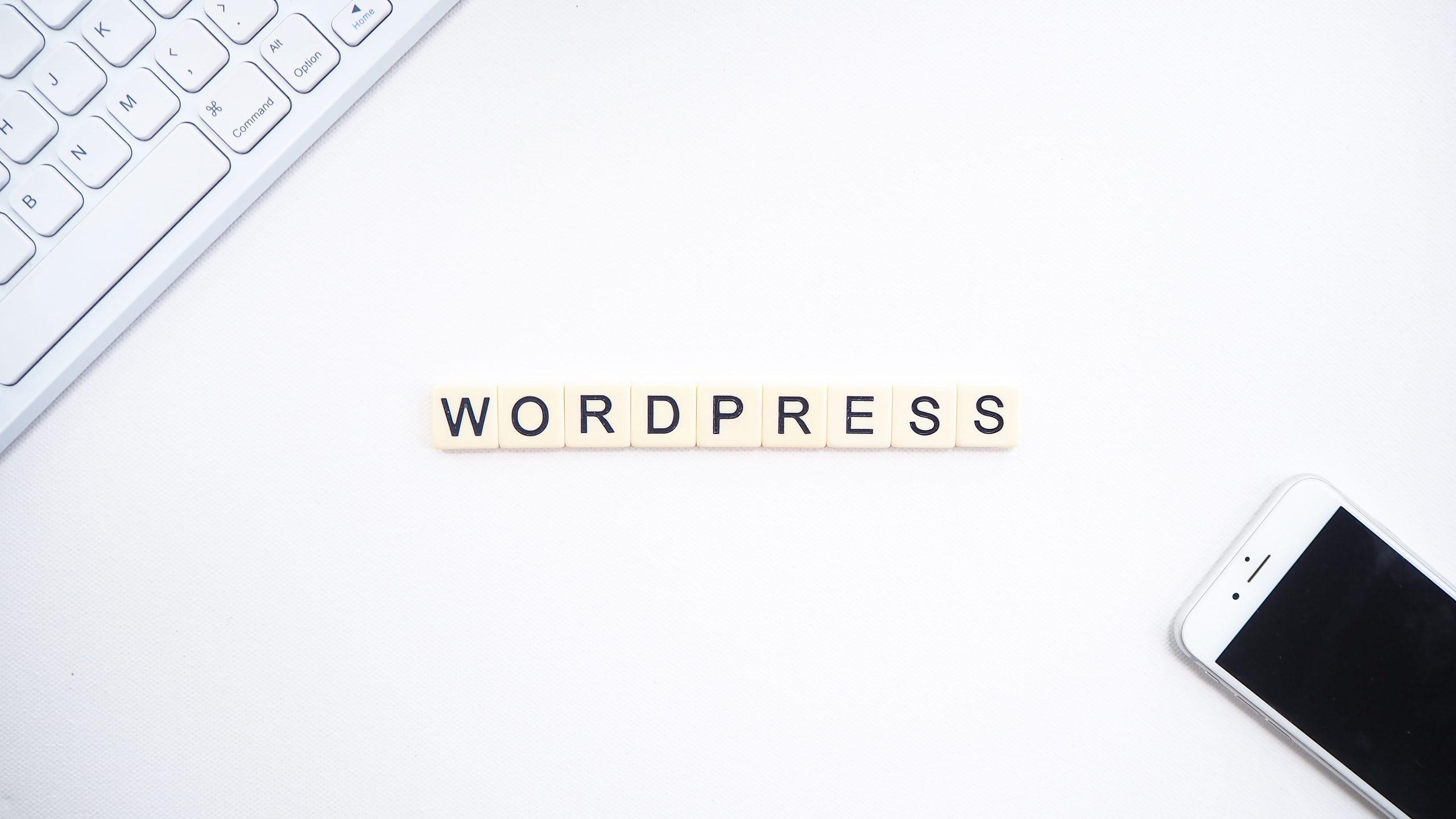 WordPressのイメージ。WordPressのロゴの隣に、キーボードとスマートフォンが表示されている。