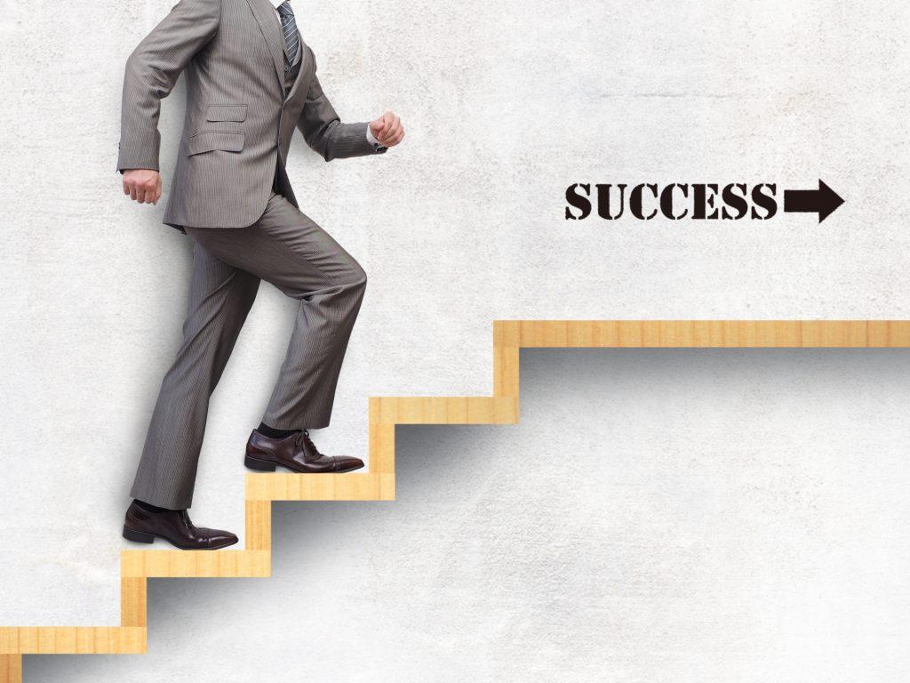 ステップアップして成功している人のイメージ。男性が階段を上り、「SUCCESS」という文字に近づいていっている。