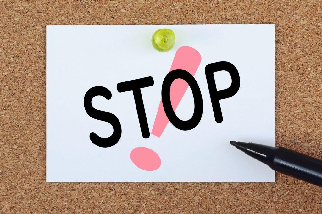 「!」マークを背景に、紙に「STOP」とペンで書かれている。