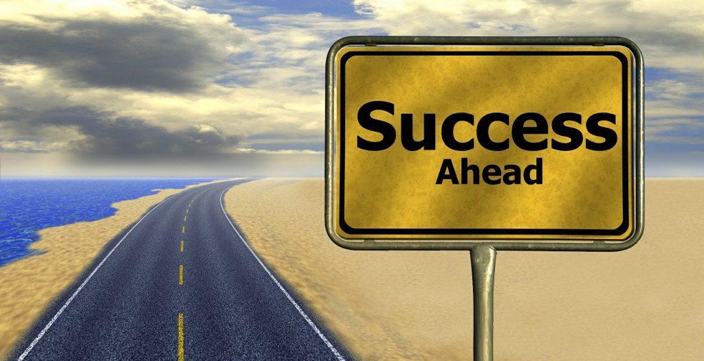 標識に「Success」と表示されている。後ろには道路が続いている。