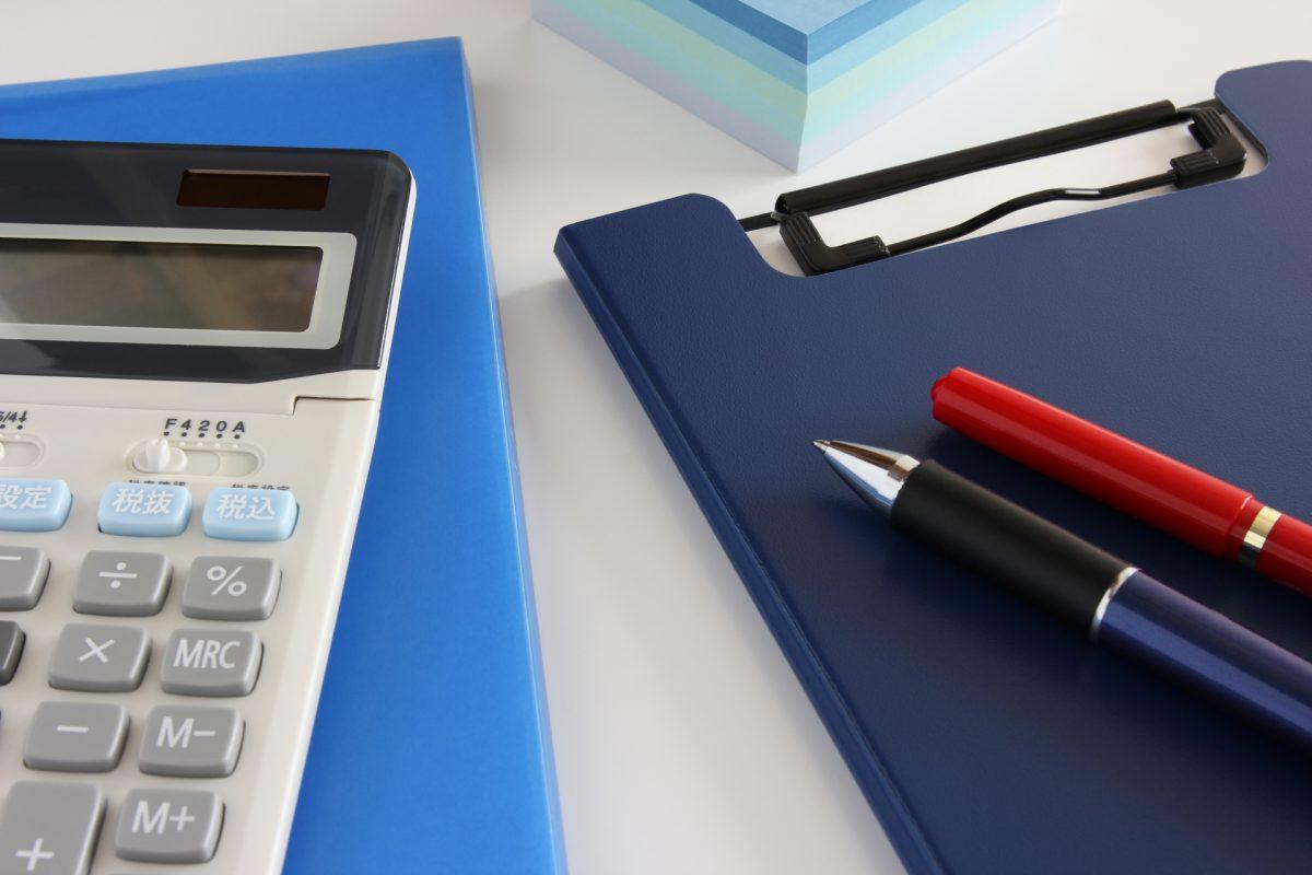 電卓とメモ帳とペンが置かれている。