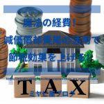 「魔法の経費!減価償却費用の活用で節税効果を上げる!」のイメージ画像。TAXと書かれた積み木の後ろに、家の模型と積み上げられたコインがある。