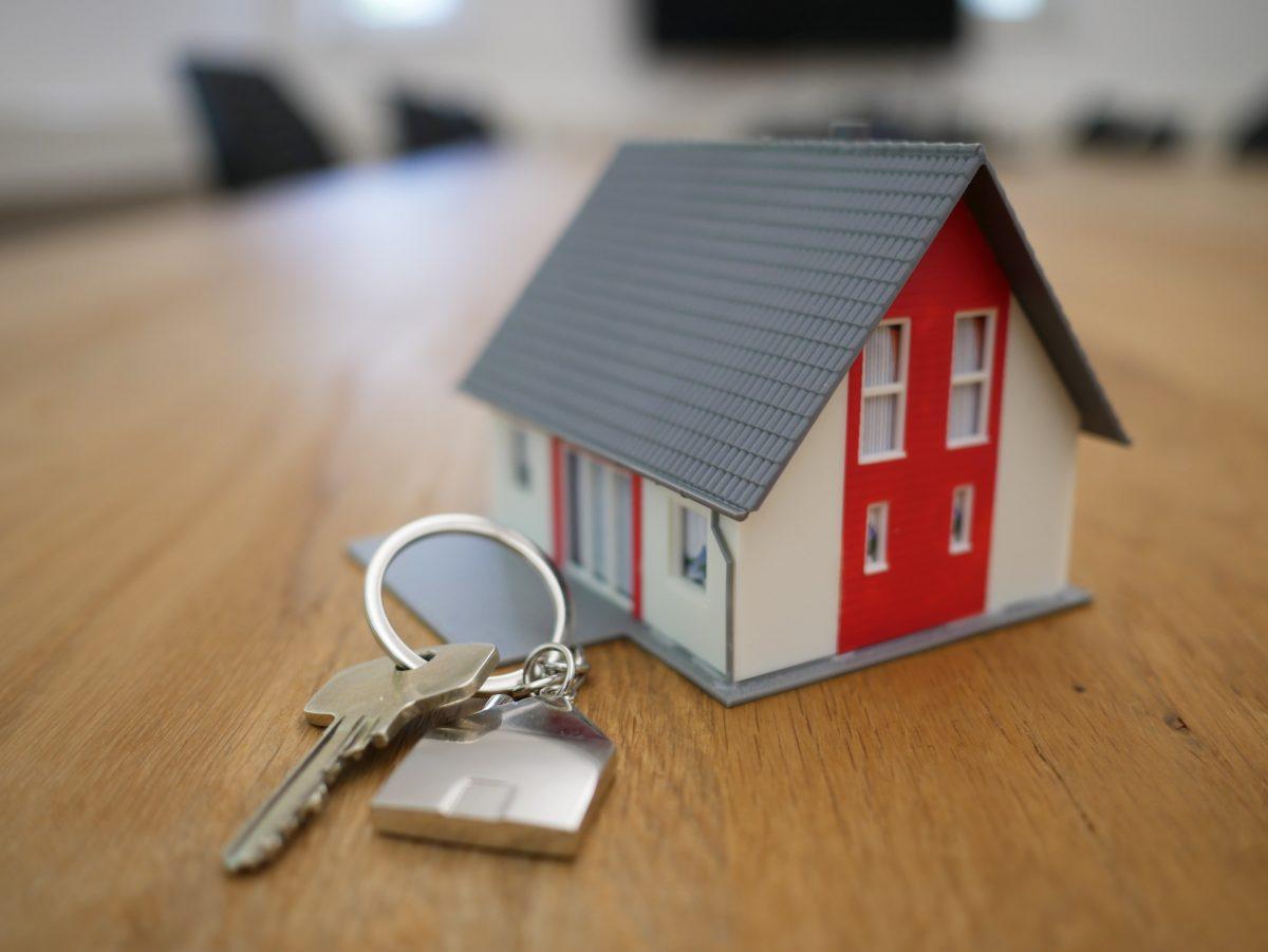 一戸建ての模型の隣に、家の鍵が置かれている。