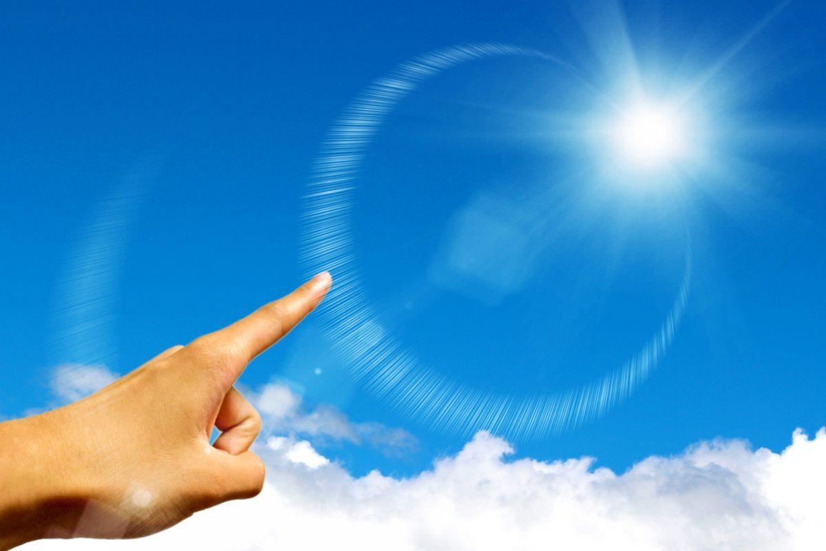 青空に輝く太陽に、人差し指を指している。