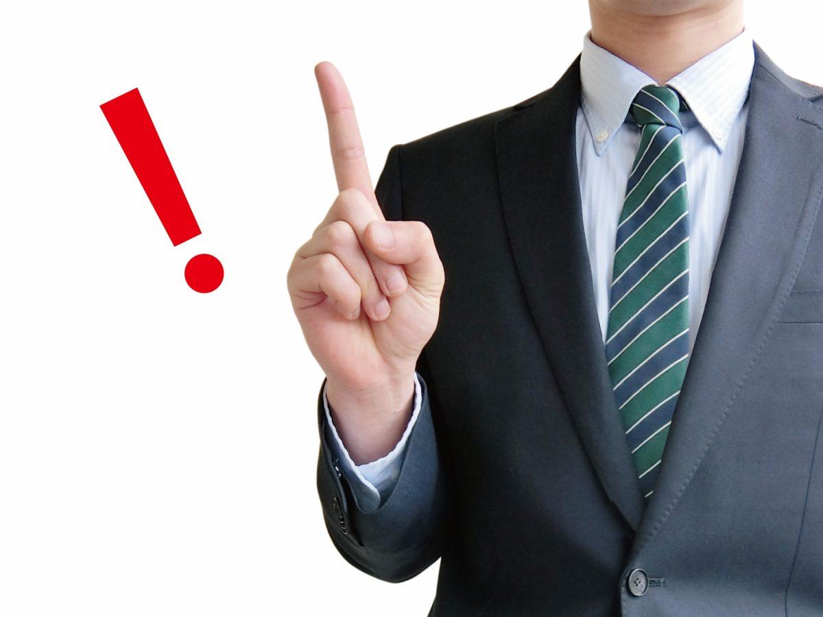 スーツを着た男性が、人差し指を立てている。その手の横に赤いビックリマークが表示されている。
