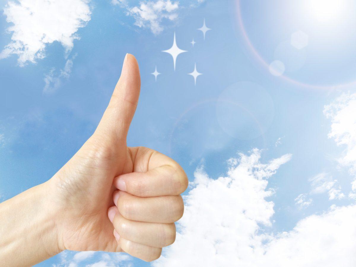 青空を背景に、親指を立てた右手が表示されている。