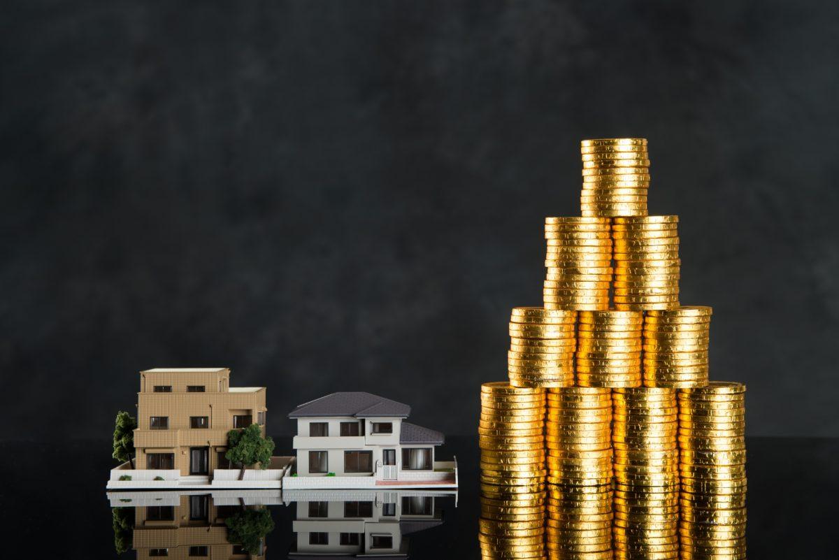 不動産の模型と、高く積み上げられたコインが並んでいる。