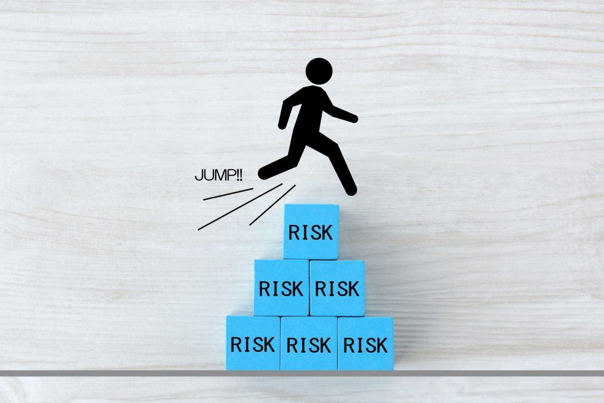 リスク回避のイメージ。リスクと書かれた正方形が、ピラミッドの形に積まれている。それを人型のイラストがジャンプして越えている。