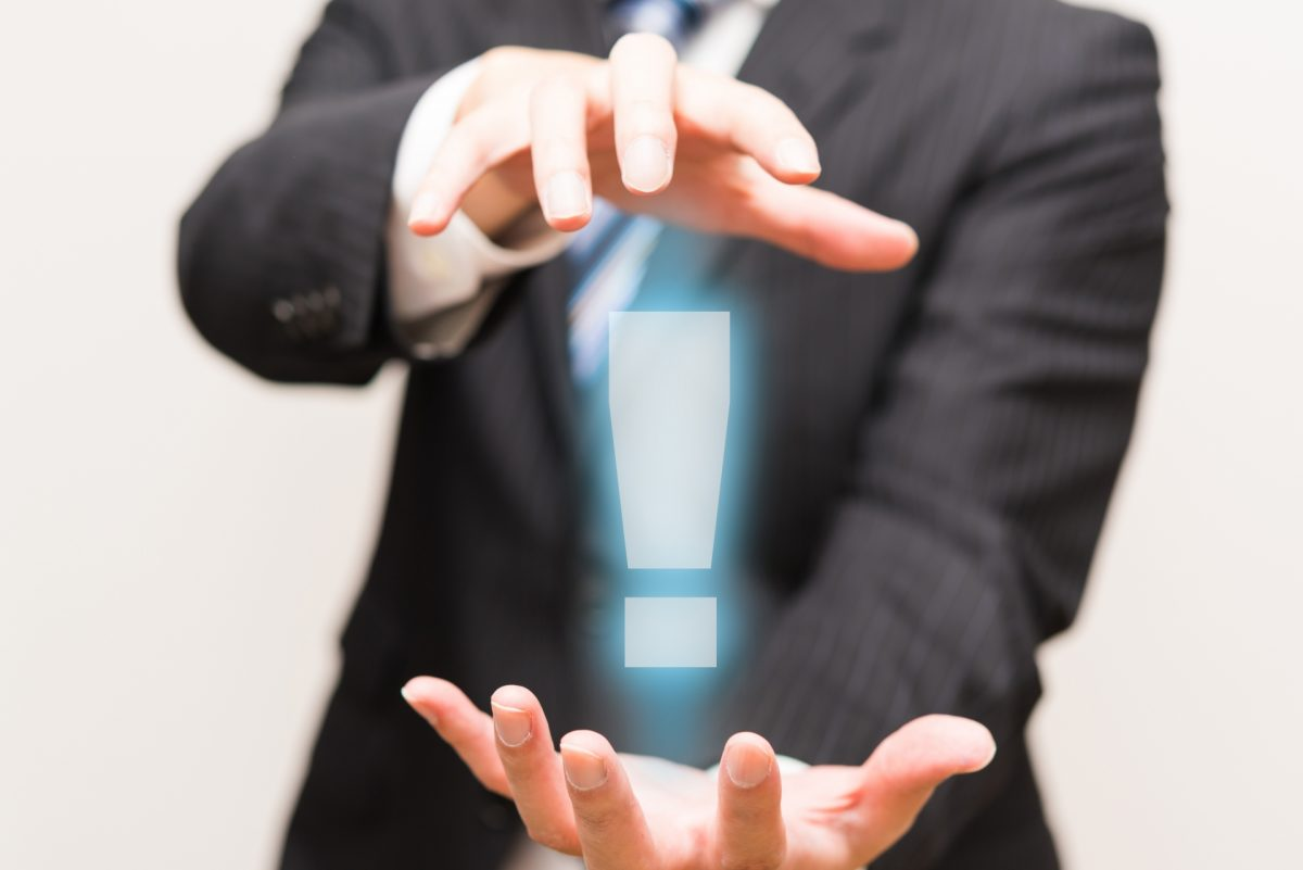 スーツを着た男性が手を前方に伸ばし手のひら同士を向かい合わせて構えている。手の間にはビックリマークが表示されている。