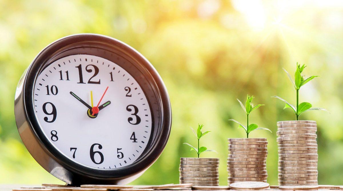 積み上げられたコインから若葉が芽吹いている。その隣には、時計が置かれている。