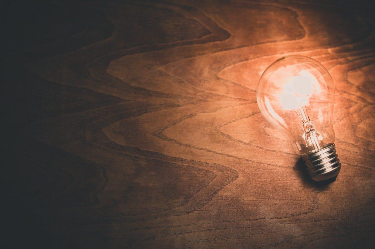 暗い部屋の木の板の上に置かれた、電球が光っている。