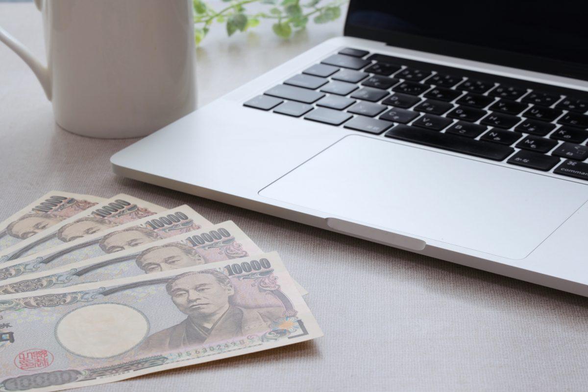 パソコンと一万円札が5枚とカップが置かれている。