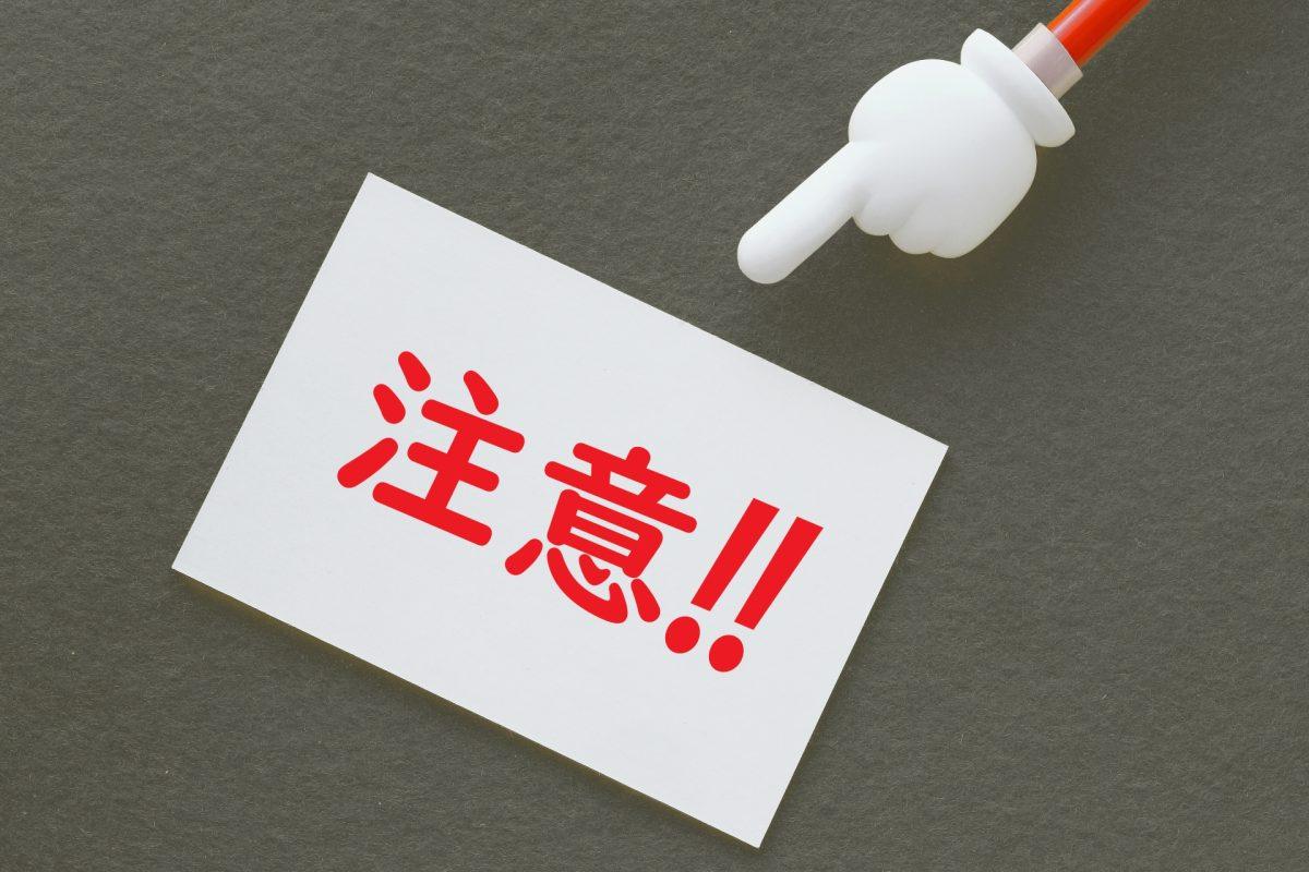 「注意」と書かれた紙を、指さし棒で指し示している。