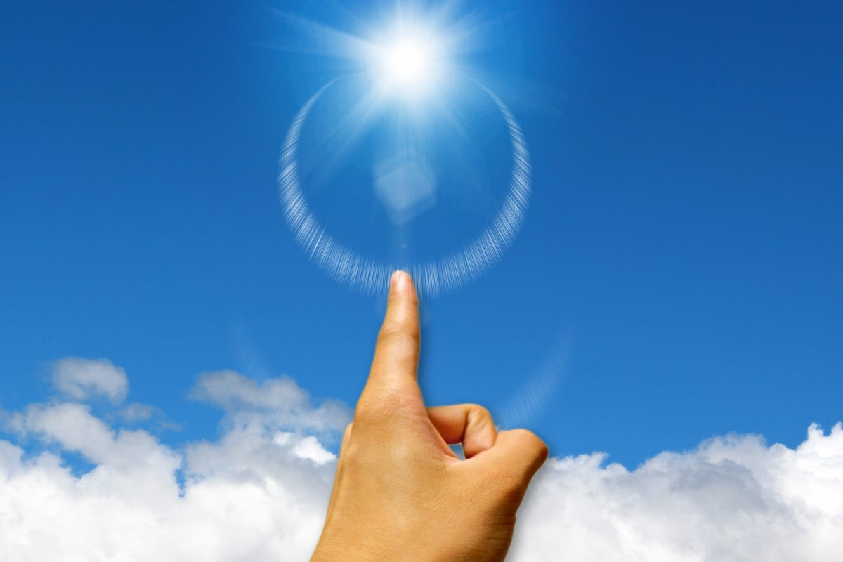 青空に輝く光に、人差し指を指している。