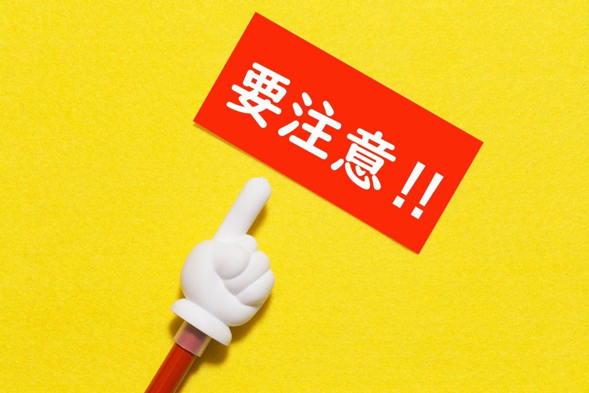 要注意と書かれた紙を、人差し指を立てた指し棒で、指し示している。