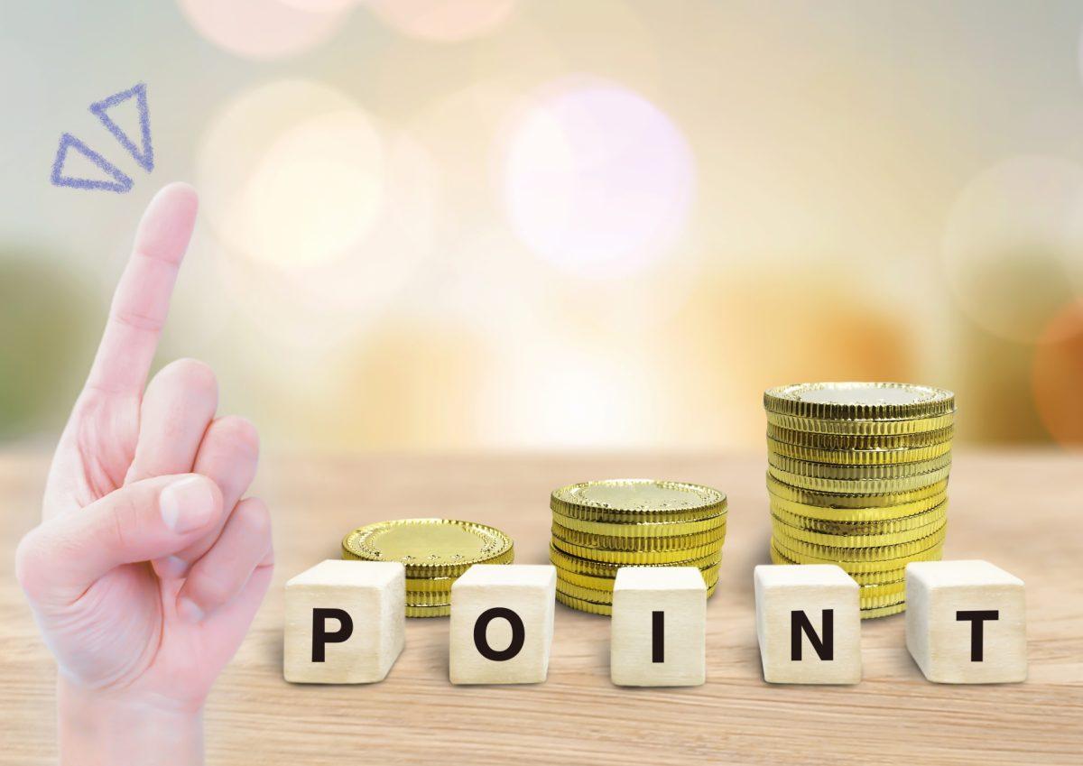 積み上げられたコインの前に、「POINT」と書かれたブロックが置かれている。その左に人差し指を立てた手が表示されている。