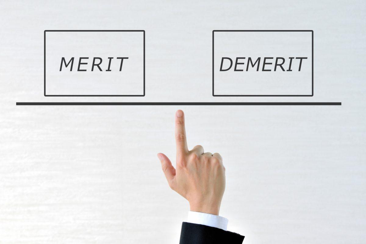 「MERIT」と「DEMERIT」を男性が人差し指を立て、天秤のように支えている。