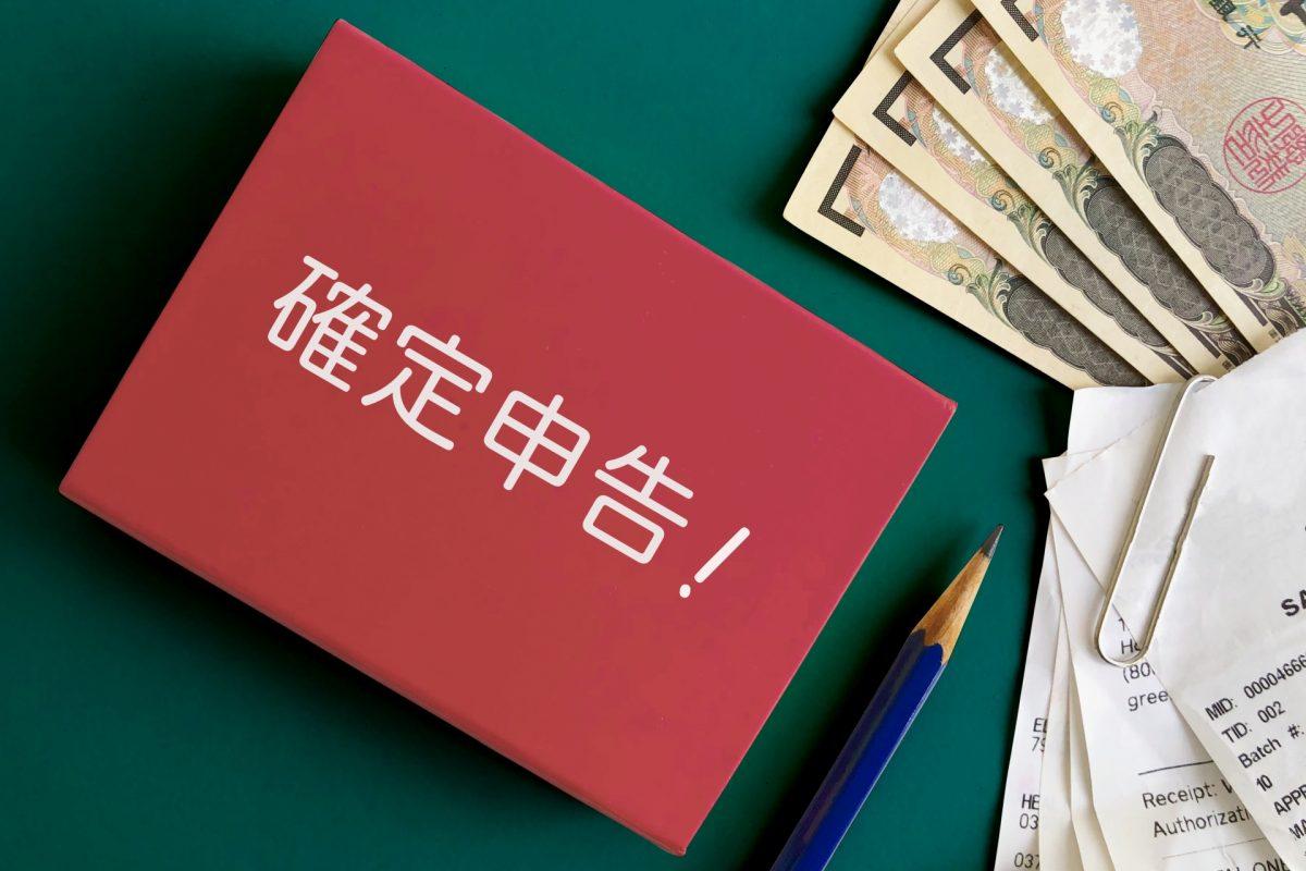 確定申告と書かれたメモの隣に、紙幣と領収書が置かれている。