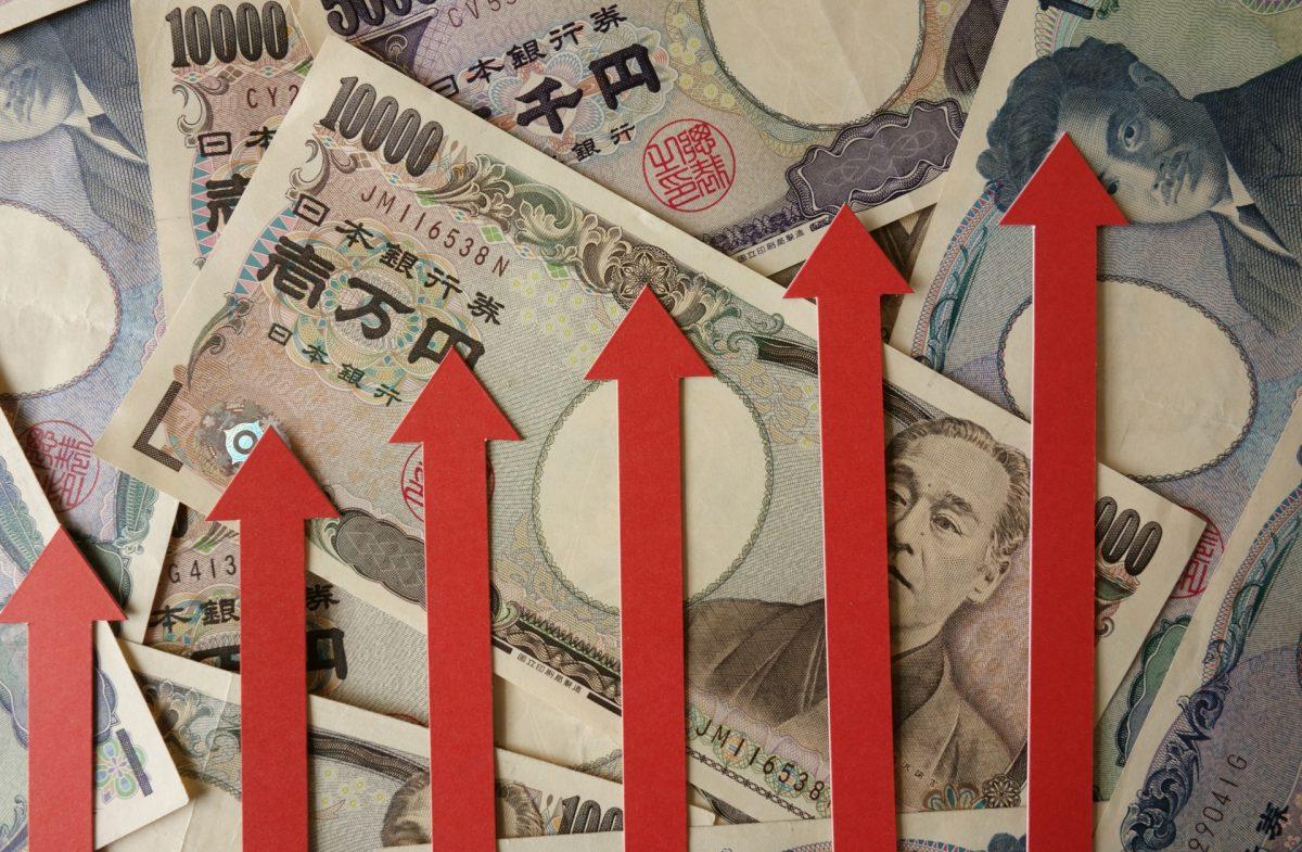 たくさんの日本紙幣の上に、赤い上向き矢印が階段状に並んでいる。