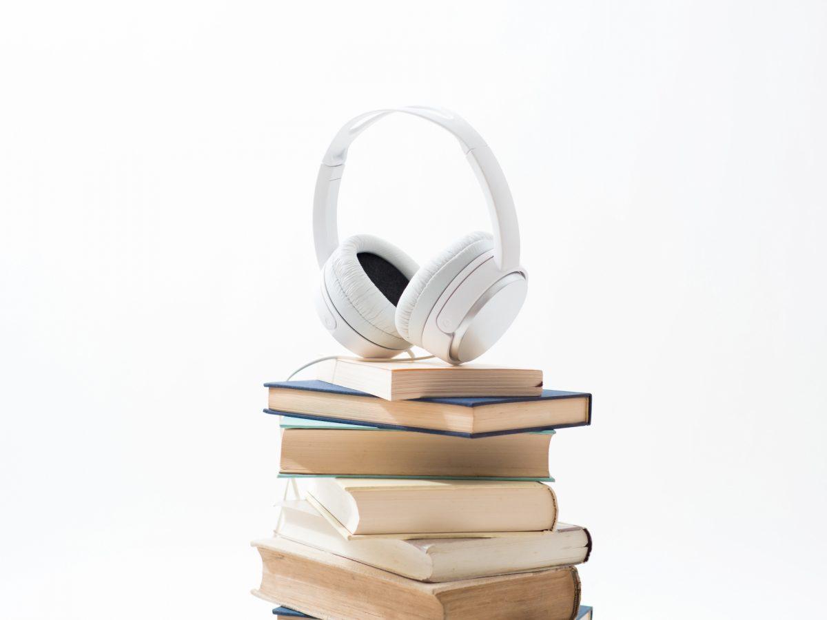 沢山の本が積み上げられた上にヘッドホンが置かれている。