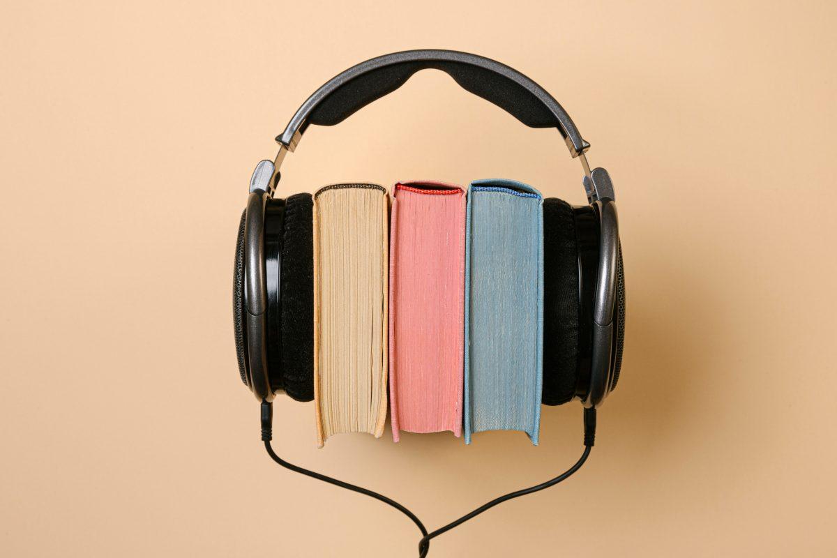 三冊の本が並べて置かれ、本が何かを聴くようにヘッドホンで挟まれている。
