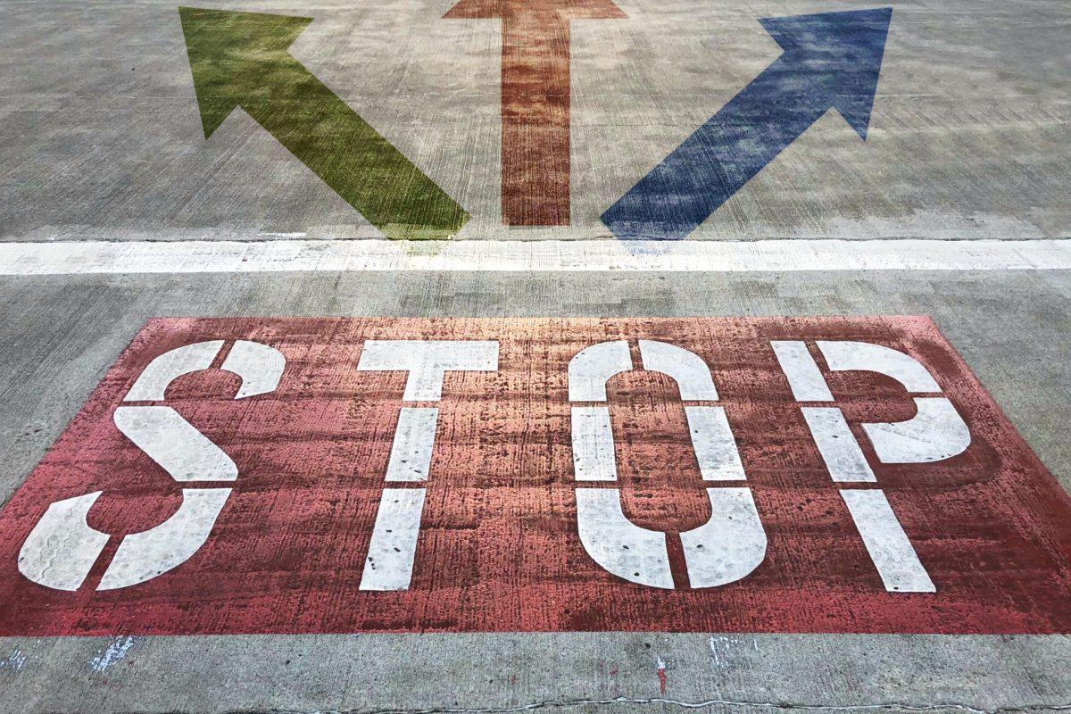 地面にSTOPと書かれ、その先に3つの矢印が分岐している。