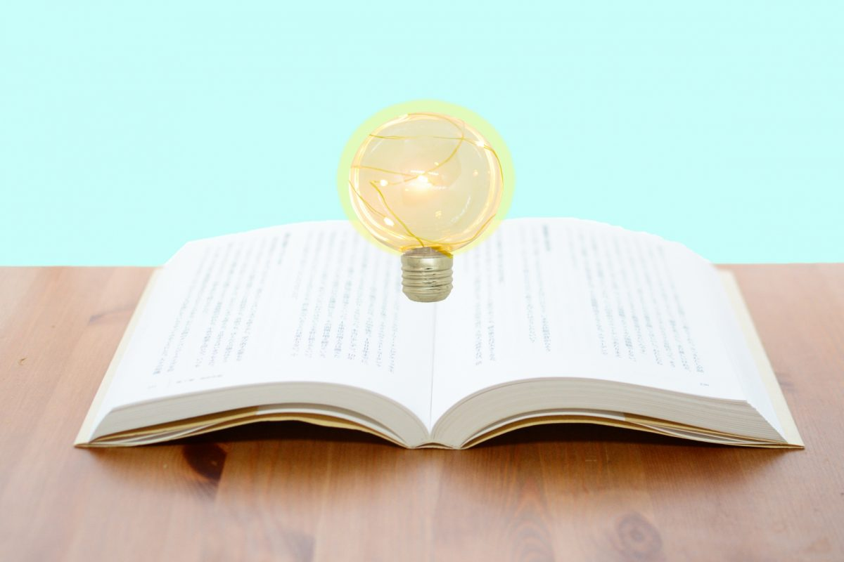 開かれた本の上に電球が浮かんでいる