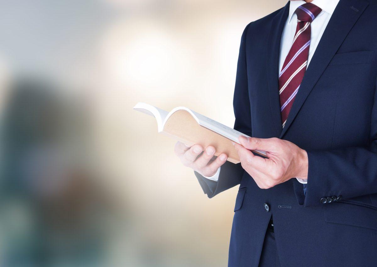 スーツの男性が本を読んでいる