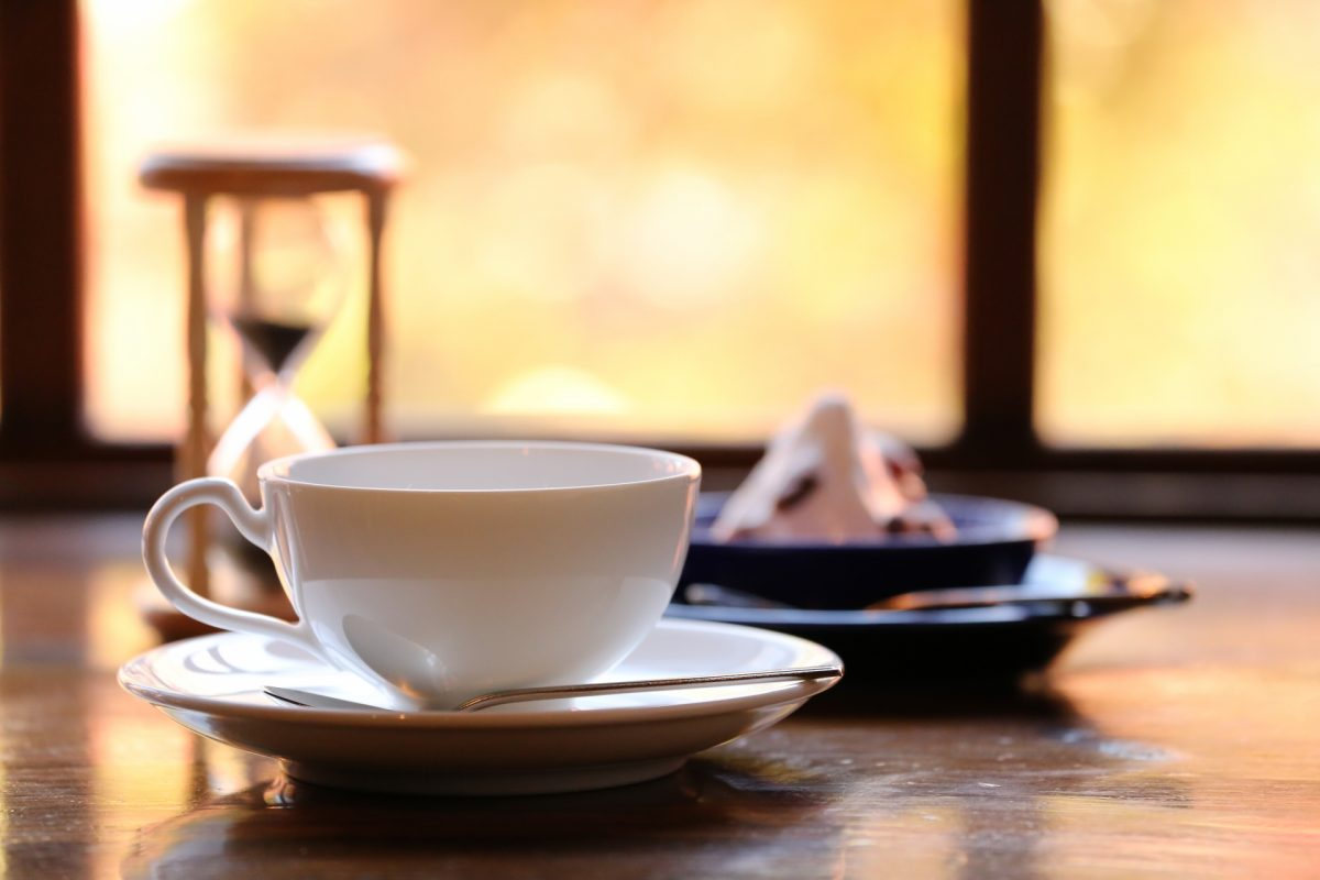テーブルにコーヒーとスイーツと砂時計が置かれている