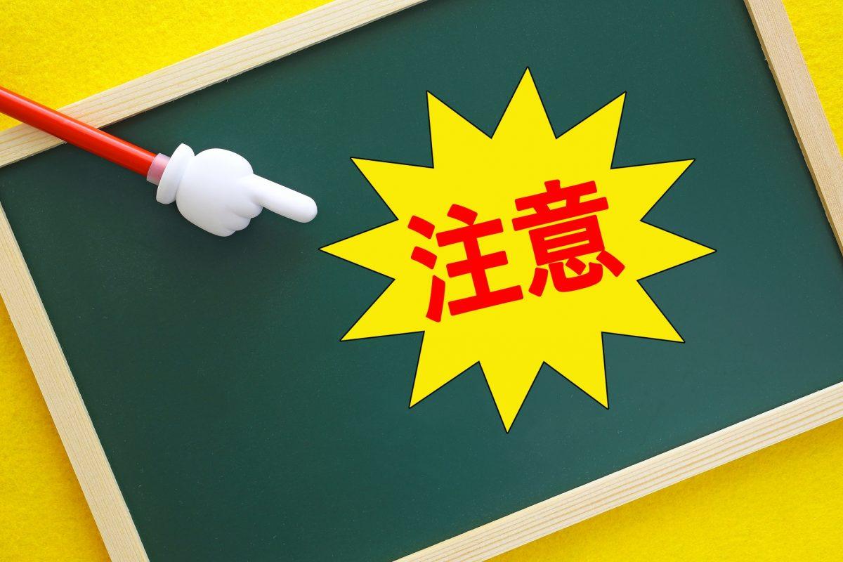 黒板に貼られた注意を、指さし棒で指している。