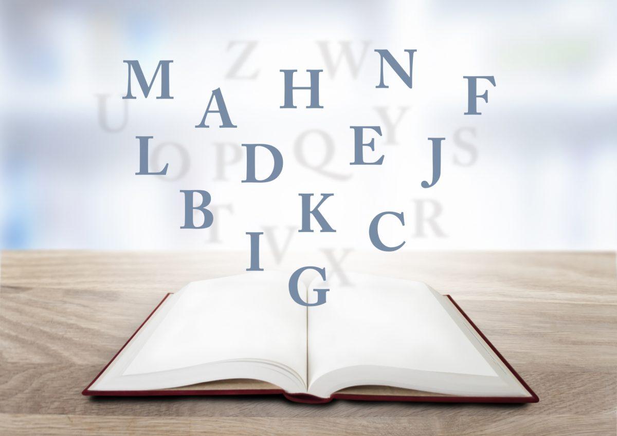 開かれた本の上にアルファベットが浮かんでいる