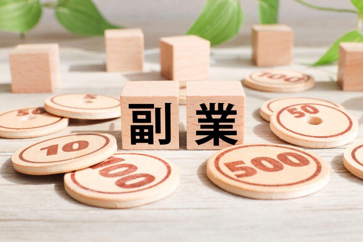 副業と描かれたブロックお周りに木製のコインが大量に置かれている