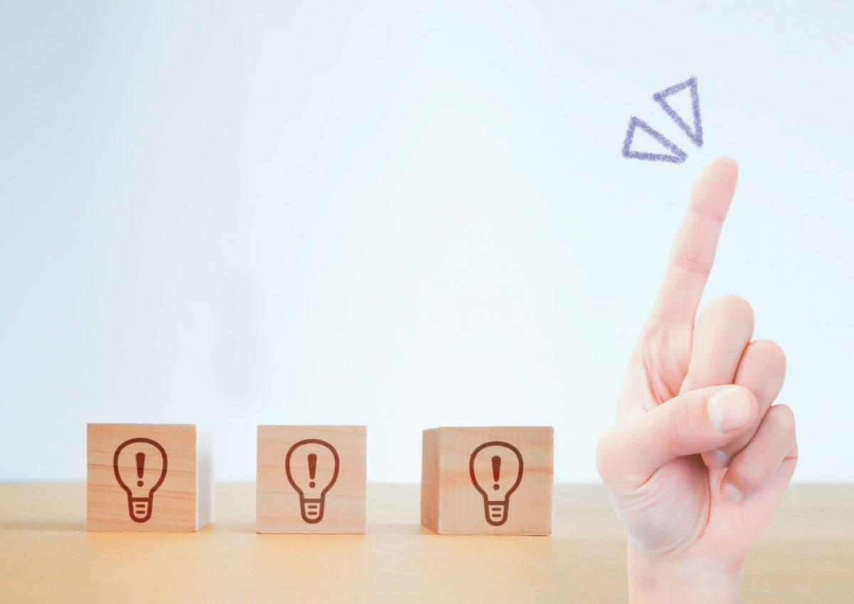 電球マークが描かれたブロックが3つ置かれた横で人差し指を立てている