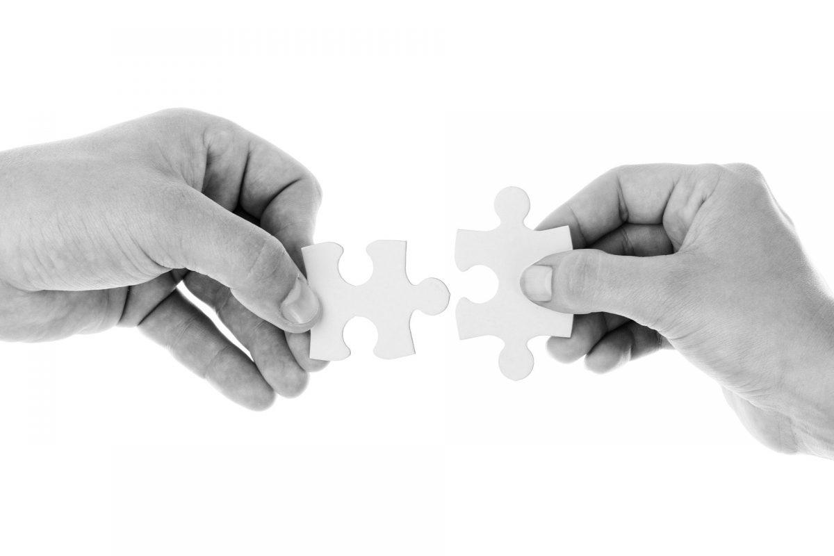 パズルのピースを持った手がピースを合わせようとしている