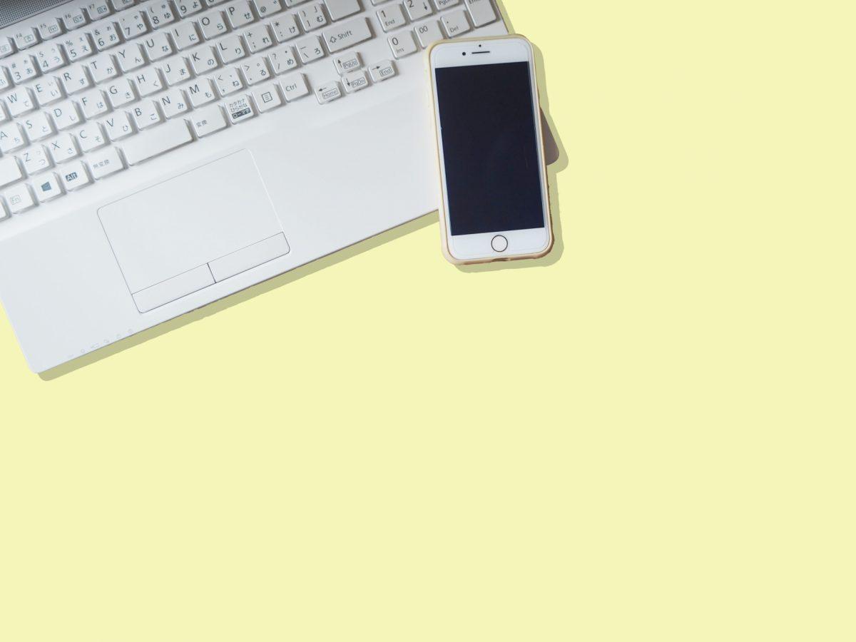 ノートパソコンのキーボードの上にとスマートフォンが置かれている