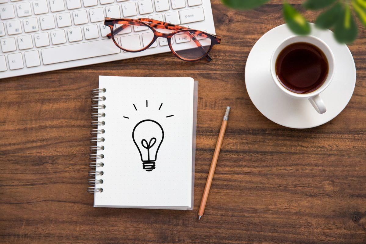 電球のイラストが描かれているメモ帳の横にコーヒーとキーボードが置かれている