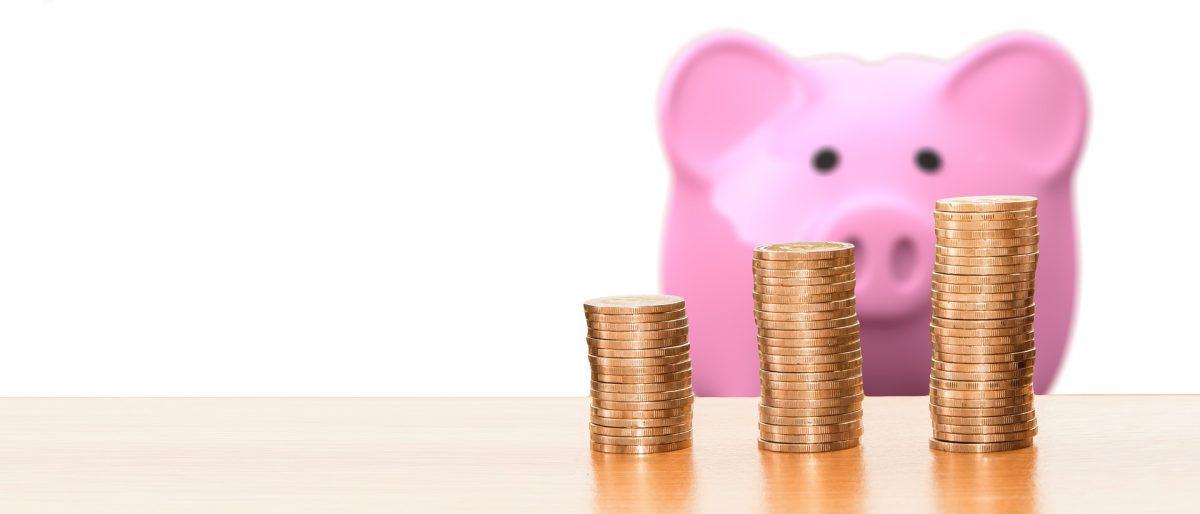 詰まれたコインと豚の貯金箱