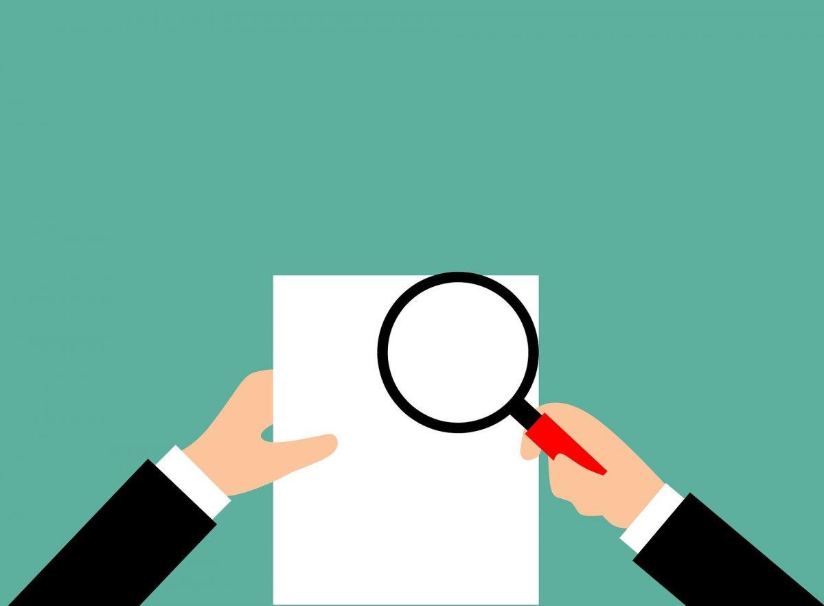書類を虫眼鏡で見るイメージ