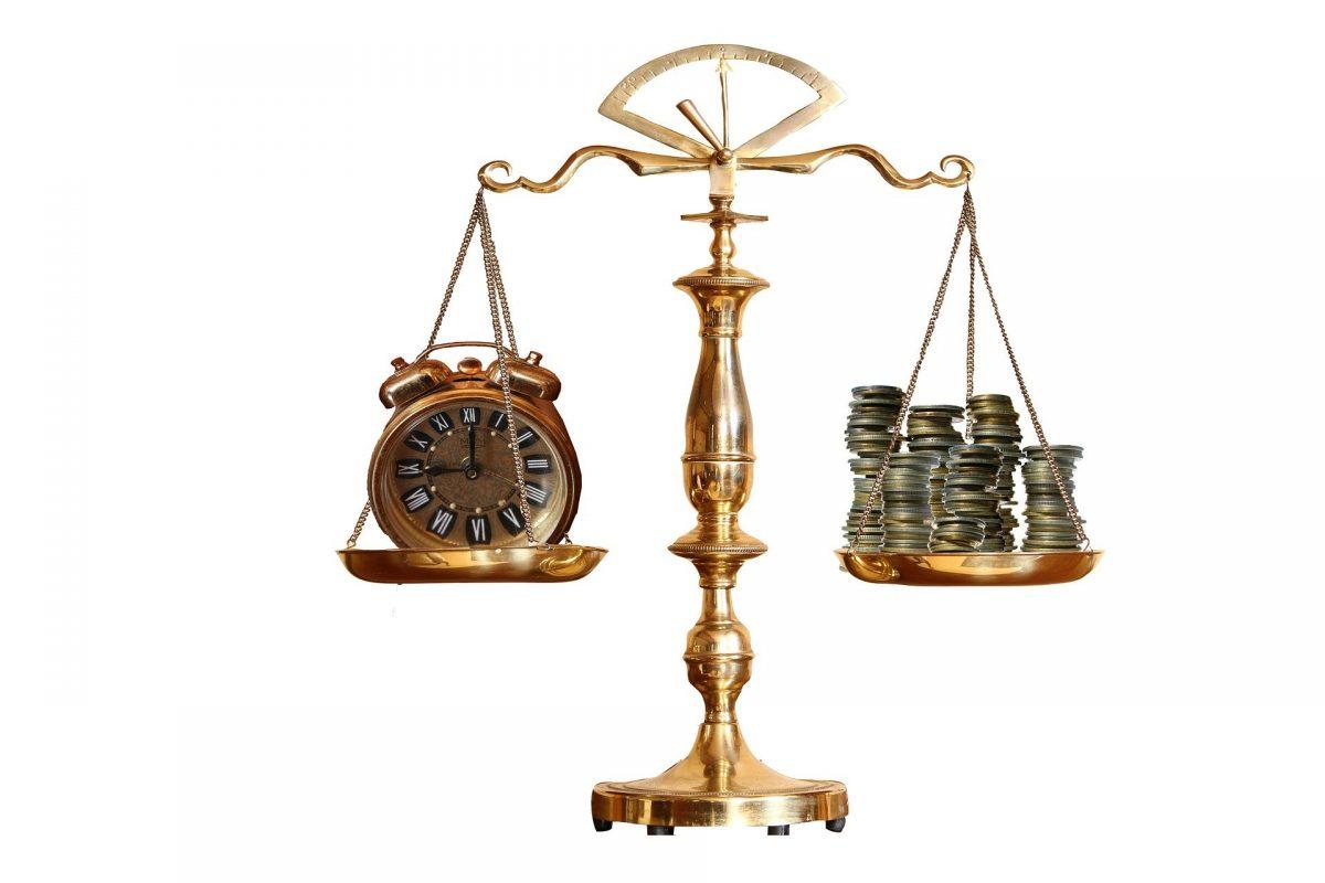 天秤に時計とお金が乗せられ均衡がとれている